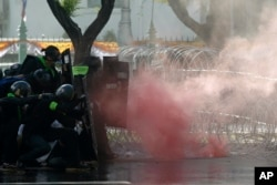 Riot police launch tear gas to protesters marching to Government House in Bangkok, Thailand Sunday, July 18, 2021.