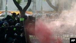 Polisi menembakkan gas air mata untuk menghentikan demonstran yang berbaris menuju kantor PM Prayuth Chan-ocha di Bangkok, Thailand hari Minggu (18/7).