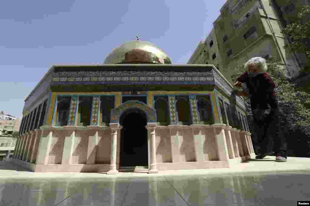 Nghệ sĩ người Jordan Nezam Nimeh, 58 tuổi, lau chùi tác phẩm nghệ thuật của mình là mô hình thu nhỏ của điện thời Mái vòm Đá ở Amman.