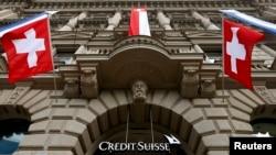 Les drapeaux nationaux de la Suisse au-dessus de l'entrée du siège de la banque Crédit Suisse à Zurich, 31 juillet 2014