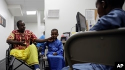 FILE - Ali Said, of Somalia, left, waits at a center for refugees with his two sons, July 6, 2017, in San Diego. Said, whose leg was blown off by a grenade, says he felt unbelievably lucky to be among the last refugees allowed into the United States befor