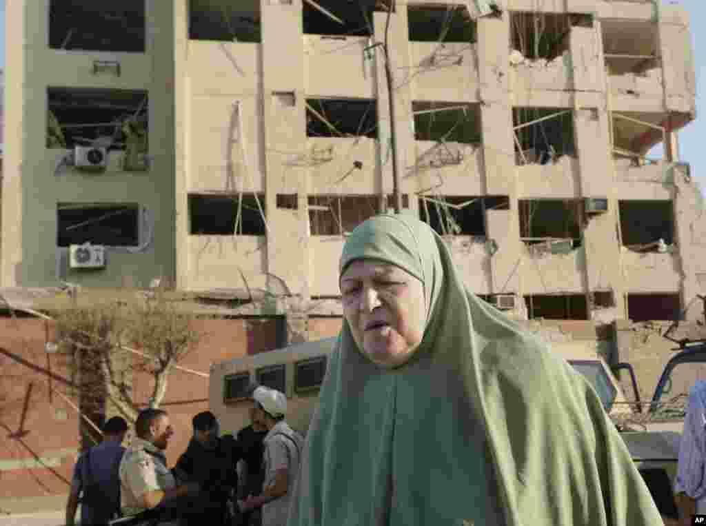 Seorang perempuan Mesir berjalan dekat gedung keamanan nasional yang rusak akibat serangan bom di daerah Shubra el-Kheima di Kairo, yang melukai beberapa orang (20/8). (AP/Amr Nabil)