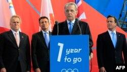 За трибуной, установленной на Трафальгарской площади в Лондоне, выступает президент Международного олимпийского комитета Жак Рогге.