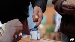 Seorang pejabat Burundi menandai jari seorang pemilih dengan tinta setelah memilih pada pemilu parlemen di Ngozi, Burundi, 29 Juni 2015.