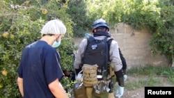 Seorang ahli senjata kimia utusan PBB (kanan) tengah mengumpulkan barang bukti di salah satu lokasi terjadinya serangan gas beracun di wilayah Mouadamiya, sebelah barat daya Damaskus (26/8).