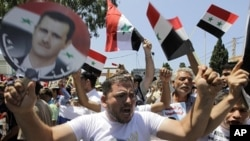 Protesters shout slogans, one of them holding a depiction of Syrian President Bashar al-Assad and a Syrian flag, during a demonstration in Beirut, Lebanon, Sunday, June 19, 2011