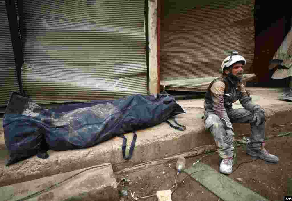 សមាជិកនៃអង្គការ White Helmets អង្គុយនៅក្បែរសាកសពរបស់ជនរងគ្រោះម្នាក់ដែលត្រូវបានគេយកចេញពីគំនរអគារបាក់បែក បន្ទាប់ពីការវាយប្រហារតាមអាកាសដោយកងកម្លាំងក្រុមឧទ្ទាមក្នុងទីក្រុង Ariha ភាគខាងជើងខេត្ត Idlib នៃប្រទេសស៊ីរី។