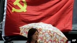 在上海,一名妇女在中共党旗下走过。中共有8000多万党员