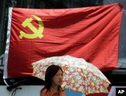 在上海,一名妇女在中共党旗下走过