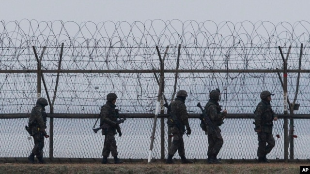 S. Korean army soldiers patrol along a barbed-wire fence near the border village of the Panmunjom, in Paju, April 8, 2013.