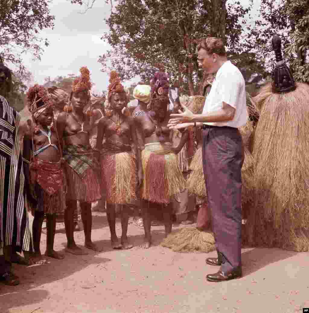 L'évangéliste américain Billy Graham parle avec les femmes d'un petit village au Ghana, en janvier 1960.