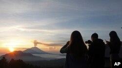 Wisatawan mengambil foto Gunung Agung pada saat matahari terbit di Kintamani, Bali, 13 Desember 2017.(AP Photo/Firdia Lisnawati)