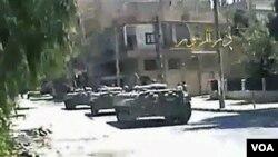 Gambar dari sebuah video amatir yang dikirim ke AP menunjukkan tank-tank tentara Suriah di jalanan kota Deir el-Zour, Selasa (9/8).