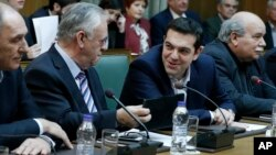 Greece's Prime Minister Alexis Tsipras, second right, and Deputy Prime Minister Giannis Dragasakis chat during the first cabinet meeting of the new government at the Parliament in Athens, on Wednesday, Jan. 28, 2015. (AP Photo/Petros Giannakouris)