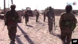 FILE - This frame grab from video released Aug. 11, 2017, and provided by Furat FM, a Syrian Kurdish activist-run media group, shows U.S.-backed Syrian Democratic Forces (SDF) fighters advance in Raqqa, Syria.