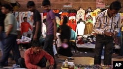 Indians walks past roadside stalls selling clothes and miscellaneous items in New Delhi, India. Indian Finance Minister, Mukherjee, presented India's new budget amid concerns about inflation, the country's falling growth rate, large deficit, FILE March 16