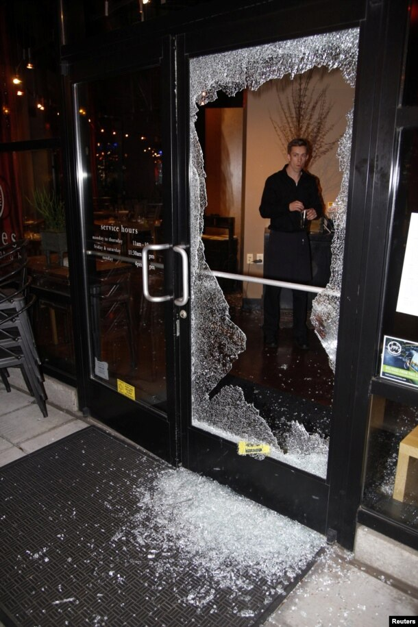 A man looks at broken glass after a riot swept through the area in protest to the election of Republican Donald Trump as President of the United States in Portland, Oregon, Nov. 10, 2016.