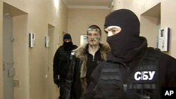 A Russian Channel One undated television grab shows a man identified as Adam Osmayev (C), one of the suspected militants conspiring to kill Vladimir Putin, walking under escort of the masked agents of the Ukrainian Security Service (SBU), shortly after hi