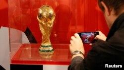 Seorang pria mengambil foto trofi Piala Dunia FIFA setelah konferensi pers FIFA World Cup Trophy Tour 2017 di Kasnoyarsk, Siberia, Rusia, 10 September 2017. ( REUTERS/Ilya Naymushin)