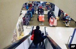 In this March 22, 2017, file photo, a woman and child ride the escalator at a Sears store in St. Paul, Minnesota.
