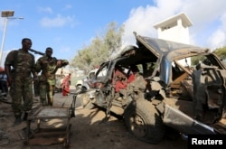 FILE - Somali policemen look at the wreckage of a car at the scene of an explosion following an attack in Somalia's capital Mogadishu, March 9, 2016.