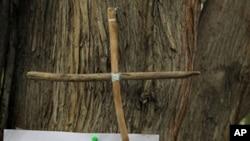 Chiếc thánh giá bằng gỗ và mảnh giấy được gắn vào thân cây, nơi ông Dimitris Christoulas tự sát