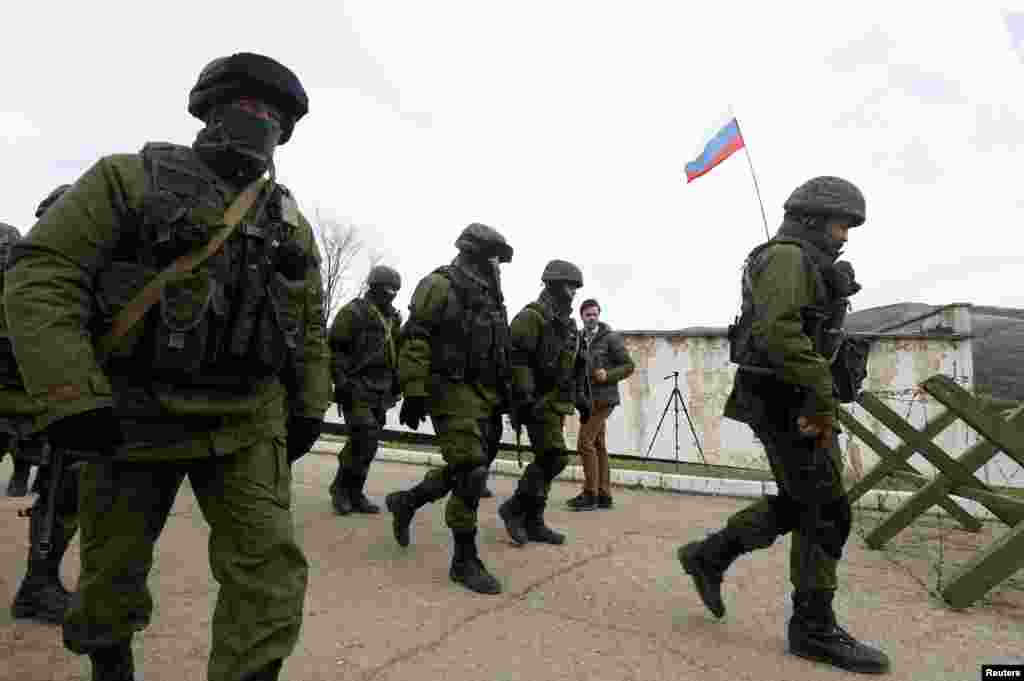 Uniformed men, believed to be Russian servicemen, walk in formation near a Ukrainian military base Perevalnoye, outside Simferopol, March 6, 2014.