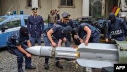 Foto yang dirilis oleh Kepolisian Turino, Italia, pada 15 Juli 2019, tampak para petugas kepolisian menggotong misil yang merupakan salah satu amunisi dan senjata yang disita oleh satuan polisi khusus. (Foto: AFP)