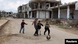 Các bé trai nô đùa gần các tòa nhà bị phá hủy tại khu vực do các nhóm đối lập kiểm soát ở Bosra al-Sham, Deraa, Syria, ngày 23/2/2016.