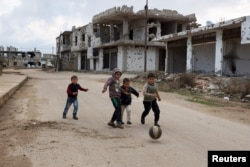 FILE - Children play near damaged buildings in the rebel-held southern town of Bosra al-Sham, Deraa, Syria, Feb. 23, 2016.