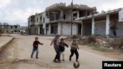 Des enfants jouent au football à proximité des bâtiments détruits dans des affrontements dans la ville historique de Bosra al-Cham, à Deraa, dans le sud de la Syrie, une ville tenue par des rebelles. (Photo prise le 23 février 2016).