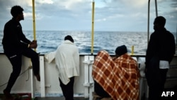 Migrants look at the coastline as they stand aboard a rescue ship, off the coast of Sicily, May 14, 2018.