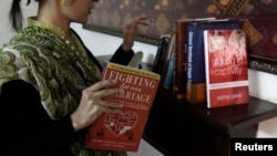 FILE - Maryam Suheyl, a marriage and family therapist, checks her books at her office in Lahore, Jan. 6, 2013.