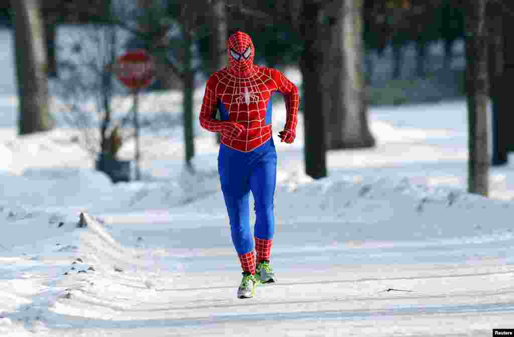 Patrick O'Brien in a Spiderman wind suit jogs around Lake Harriet in south Minneapolis, Minnesota, USA. A blast of Arctic air gripped the mid-section of the U.S., bringing the coldest temperatures in two decades, forcing businesses and schools to close and causing widespread airline delays and hazardous driving conditions.