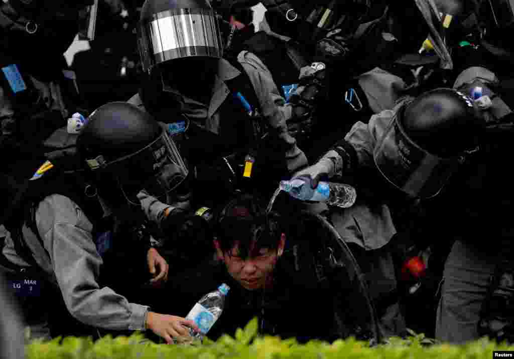 Riot police pour water on the face of an anti-government protester who was pepper sprayed while getting detained after an anti-parallel trading protest at Sheung Shui, a border town in Hong Kong.