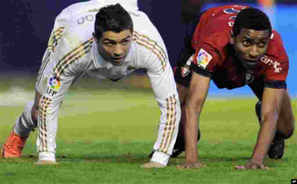 Real Madrid's Cristiano Ronaldo from Portugal, left, falls on the pitch with Osasuna's Roversio Rodrigues from Brazil during their Spanish La Liga soccer match, at Reyno de Navarra stadium in Pamplona, northern Spain, Saturday March 31, 2012. Real Madri