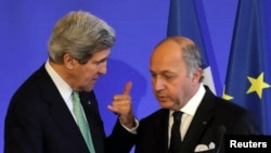 French Foreign Affairs Minister Laurent Fabius (R) listens to U.S. Secretary of State John Kerry after a news conference at the ministry in Paris, February 27, 2013.