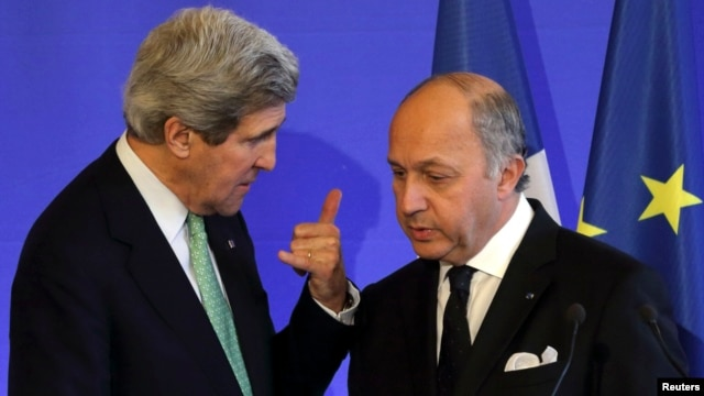 French Foreign Affairs Minister Laurent Fabius (R) listens to U.S. Secretary of State John Kerry after a news conference at the ministry in Paris, Feb. 27, 2013.