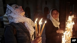 A worshiper holds candles as she prays inside the church of Holy Sepulcher in Jerusalem's Old City, April 24, 2011