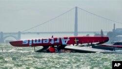 """Perahu layar catamaran """"The Artemis Racing AC72"""", peserta lomba Piala Amerika dari Swedia, terbalik saat latihan di lepas pantai San Francisco, Kamis (9/5). Atlet Inggris Peraih medali emas Olimpiade Beijing 2008, Andrew """"Bart"""" Simpson, emas Olimpiade peraih medali dari Inggris, meninggal dunia setelah terjebak di bawah perahu terbalik tersebut selama 10 menit. Jembatan """"Golden Gate"""", yang identik dengan kota San Francisco tampak sebagai latar belakang foto ini. (AP Photo / Noah Berger)"""