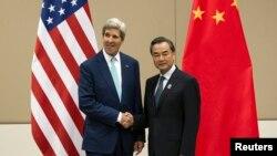 美國國務卿克里(左)和中國外長王毅(右)在東盟外長會議上會面握手。