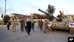 Pasukan keamanan Irak dan aliansi militan Syiah merayakan kemenangan mereka di depan gedung pemerintah di Tirkit, 130 kilometer utara Baghdad, Irak, 31 Maret 2015 (AP Photo/Khalid Mohammed)
