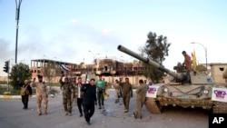 ກອງກຳລັງຮັກສາຄວາມໝັ້ນຄົງ ແລະ ກອງທະຫານບ້ານຊາວ Shiite ທີ່ເປັນພັນທະມິດ ສະເຫຼີມສະຫຼອງ ຢູ່ດ້ານໜ້າຂອງອາຄານປົກຄອງແຂວງ ໃນເມືອງ Tikrit ທີ່ຫ່າງອອກ ໄປຈາກນະຄອນຫຼວງ Baghdad ທາງທິດເໜືອ 80 ມາຍ ຫຼື 130 ກິໂລແມັດ, ວັນອັງຄານ ທີ 31 ມີນາ 2015.