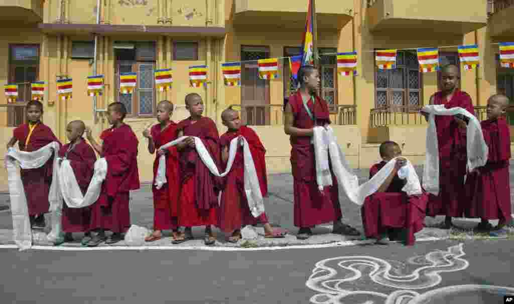 ព្រះសង្ឃនិរទេសខ្លួនទីបេ គង់ចាំដោយមានកាន់កន្សែងបង់កបែបសាសនា ដើម្បីស្វាគមន៍សម្តេចសង្ឃ ដាឡៃ ឡាម៉ា (Dalai Lama ) មុនពេលព្រះអង្គយាងមកឡើងថ្លែងសង្ឃដីកាអំពីសាសនា នៅវត្ត Gyuto Monastery ក្នុងទីក្រុង Dharmsala ប្រទេសឥណ្ឌា។