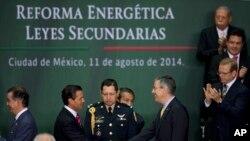El presidente Peña nieto saluda al presidente de la Cámara, José González, durante la firma de de la ley energética.