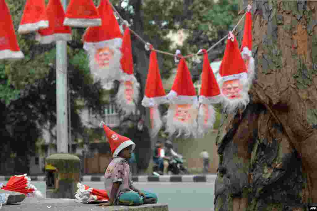 A young Indian hawker, selling Santa Claus hats and masks at a traffic junction, takes a break from work in Bangalore. Despite Christians forming only a little over two percent of the billion-plus population in India, with Hindus comprising the majority, Christmas is celebrated with fanfare and zeal throughout the country.