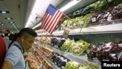 Một người mua hàng tại một siêu thị ở Hà Nội bên các sản phẩm hoa quả nhập khẩu từ Mỹ. Hàng hóa Mỹ nhập khẩu vào Việt Nam đã tăng mạnh trong 6 tháng đầu năm nay do thương chiến Mỹ-Trung.