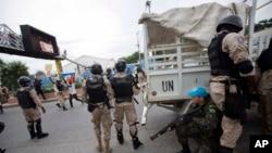 Foto Archivo - Un guardia de paz de Estados Unidos se esconde detrás de los policías nacionales mientras los manifestantes lanzan piedras durante una protesta contra el consejo electoral del país para celebrar el 25 aniversario de la primera elección democrática en 1990 en Puerto Príncipe, Haití.