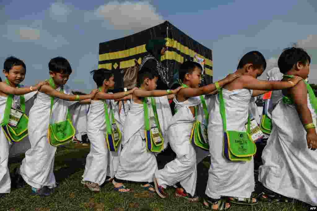 "Anak-anak Muslim Malaysia mengelilingi model ""Ka'bah"" pada acara simulasi ibadah Haji di sekolah mereka."