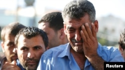 Omar Al-Zuhbe, right, father of Belal Al-Zuhbe, one of the solders killed in an attack on a border military post near a camp for Syrian refugees, cries during his son's funeral in Jerash, north of Amman, Jordan, June 21, 2016.